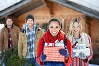 Portrait of smiling couples holding fresh cut Christmas tree and gifts (thumbnail)