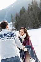 Smiling couple holding hands in snowy field