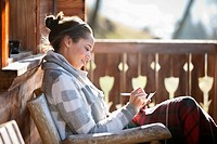Smiling woman with paper and pen on cabin porch (thumbnail)