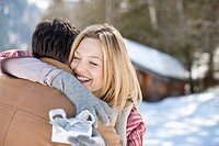 Smiling woman holding Christmas gift and hugging man in snowy field