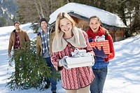 Portrait of smiling couples with fresh cut Christmas tree and gifts in snow
