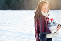 Portrait of smiling woman carrying Christmas gifts in snow (thumbnail)