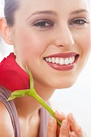 Close up portrait of smiling woman holding red rose