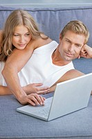 Couple laying on sofa and using laptop