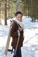 Portrait of smiling woman holding sled in snowy woods