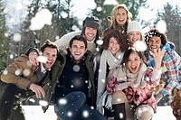 Portrait of smiling friends throwing snow