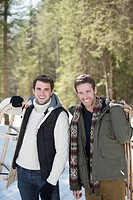 Portrait of friends holding sleds in snowy woods
