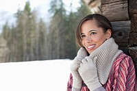 Smiling woman leaning against cabin wall in snow