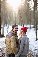 Portrait of smiling couple holding hands in snowy woods