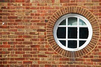 round and vintage wooden window on a brick wall building