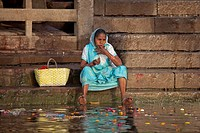 Old Indian woman cleaning her teeth with finger in polluted water of the Ganges river at Varanasi, Uttar Pradesh, India