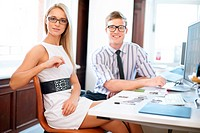 Portrait of male and female co workers looking at camera sitting behind a desk