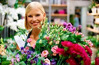Cute young florist holding an armful of fresh flowers with a smile