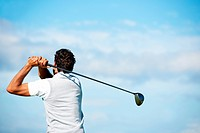Mature golfer swinging his golf club out on the course _ rear view with copyspace