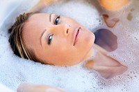 Portrait of a beautiful young woman submerged in a bubble bath