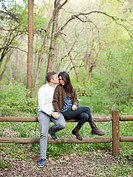 Young couple sitting on fence