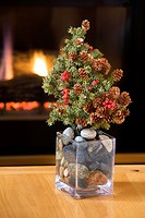 Small Real Fur Tree Decorated With Cones And Red Berries Christmas Tree On A Table In Glass Vase Filled With Round Stones And A Glowing Firplace In Th...