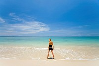 A Woman Tourist Stands In The Shallow Clear Waters Of A Tropical Island, Koh Lanta Thailand