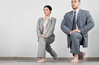 Young businesswoman and businessman doing yoga lunge side by side in office