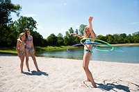 Three girls in bikinis with hula hoop at bathing lake