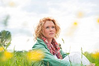 Pensive young woman sitting in meadow