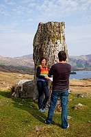 A Man Taking A Picture Of A Woman Beside A Rock Formation On The Coast Near Kenmare, County Kerry Ireland