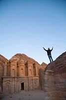 A Woman Tourist Raises Her Arms In Front Of The Nabatean Ruins Of The Monastery, Petra Jordan