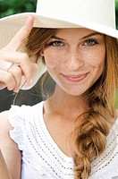 Smiling young woman wearing sunhat, portrait