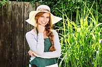 Smiling young woman wearing sunhat and apron in garden