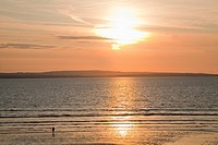 Silhouette of a person standing on the beach at the water´s edge at sunset, inishcrone county sligo ireland