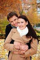 Glückliches Paar schmiegt sich im Herbst im Park aneinander