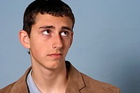 Teenage young man looking up with a worried expression