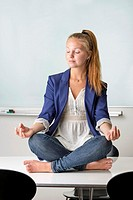 Attractive businesswoman sitting barefoot in yoga position on a table in her workplace