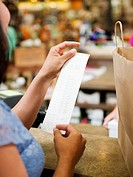 Mixed race woman looking at shopping receipt