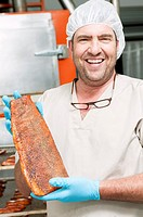 Hispanic cook holding smoked salmon