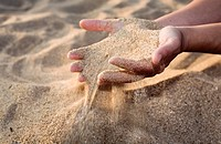 close-up of woman hands caressing beach sand