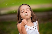 Mixed race girl blowing dandelion seeds