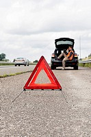Warning triangle on the shoulder of a motorway behind a stalled car, with the owner and driver making a phone call, sitting in the booth of his vehicl...