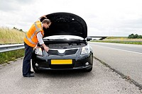 Man wearing a safety vest checking under the hood of his broken down car on the hard shoulder of a motorway