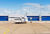 Propellor aircraft and maintenance cart in front of hangars on the airstrip of a small airport
