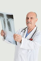 Portrait of serious senior male doctor holding medical radiograph over gray background