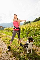 Caucasian woman with dog stretching in vineyard