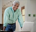Black man standing with laptop