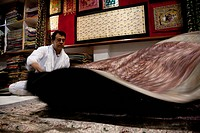 Indian man shaking carpet
