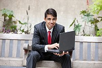 Young Indian businessman using laptop while sitting on bench
