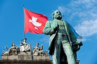 Swiss flag flying behind the statue of Alfred Escher, Swiss politician, business leader and railway pioneer, by Richard Kissling, square in front of t...