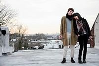A young couple standing on a roof in winter, smoking cigarettes