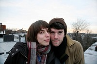 A young couple standing side by side on a roof in winter, Brooklyn, New York