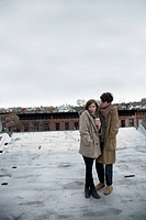 A young couple standing on a roof in winter, Brooklyn, New York