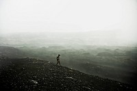 A hiker walking through the fog, Plosky Tolbachik Volcano, Russia